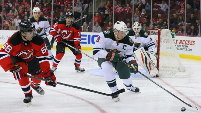 Minnesota Wild center Mikko Koivu (9) controls the puck against New Jersey Devils right wing Jaromir Jagr (68) during the first period at the Prudential Center.