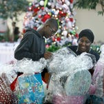 Lunden Thomas,15, of Rochester helps his mother Lonese Sampson, owner of Pink Elegance, wrap gift baskets during the first annual Black Business Marketplace event at the Sibley Building.
