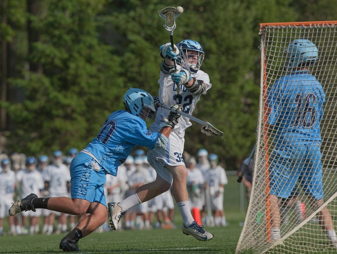 CBA's Michael Convery scores a second half goal as Notre Dame's Nico Sferra tries to knock him off his shot. CBA vs Notre Dame in NJSIAA  Boys State Lacrosse in Middletown, NJ on May 20, 2014. Photo by Peter Ackerman