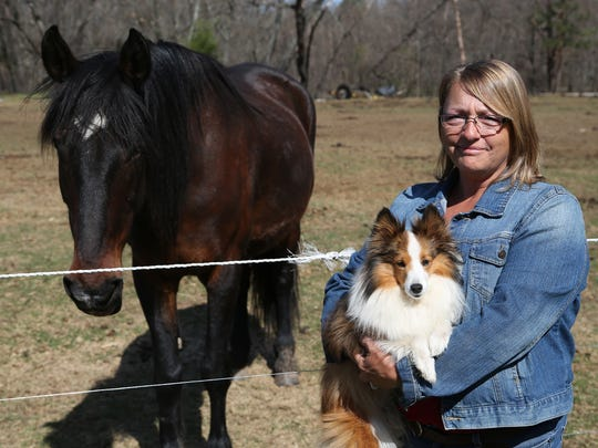 Kathy Diedrick is shown at her Babcock home with one of her horses and one of her dogs on April 28, 2015.