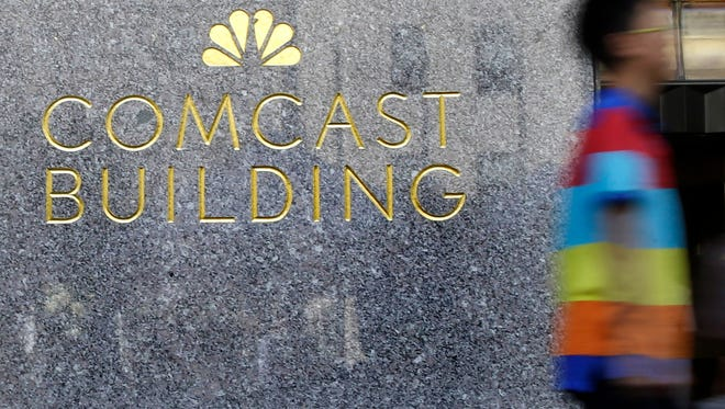 In this July 23, 2015, file photo, a man walks past the Comcast Building in New York. (AP Photo/Mary Altaffer, File)