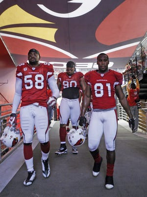 Karlos Dansby #58 walking into the locker room with Anquan Boldin #81 and Darnell Dockett #90.