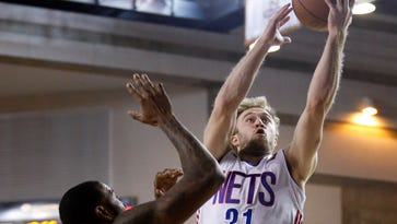 Former Sanford and Syracuse star Trevor Cooney of the Long Island Nets cuts to the hoop against the 87ers' Terrence Jennings (left) and Russ Smith as Cooney returns to Delaware in NBA D-league action.