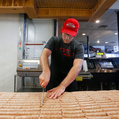 Corey Milam, with Hšörrmann Meats, slices sausage into
