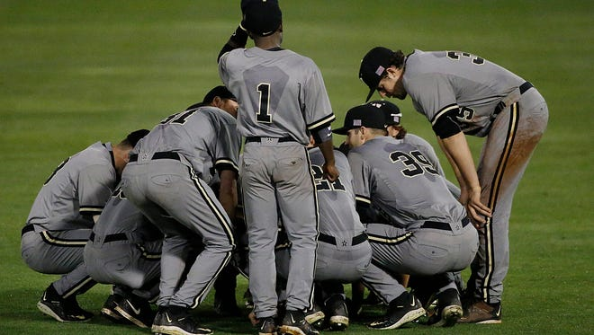 Vanderbilt players huddle in the outfield in the ninth inning of the SEC Championship game.