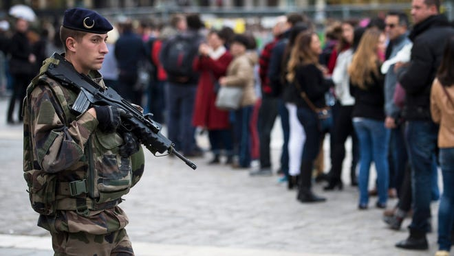 A French soldier stands guard as tourists line up to enter Notre Dame cathedral in Paris.