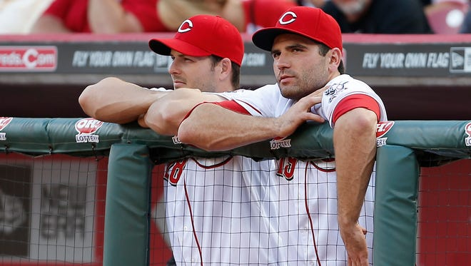Chris Heisey (28) and Joey Votto (19) watch the action in the first inning at Great American Ball Park on Tuesday against the Giants.