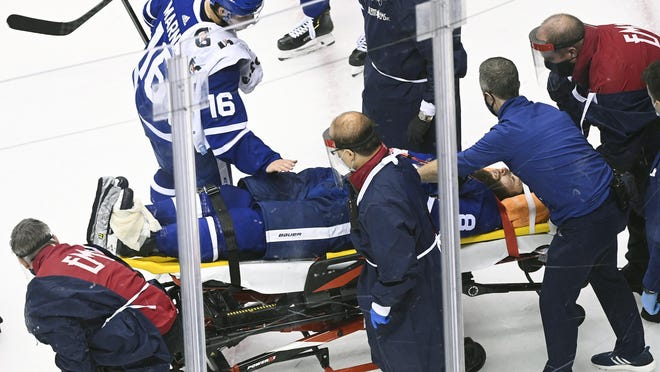 The Maple Leafs' Jake Muzzin leaves the ice on a stretcher as teammate Mitch Marner offers him encouragement during the third period of Tuesday's game.