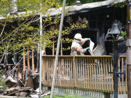 Firefighters remove debris after a Sunday house fire that left one unidentified resident dead.