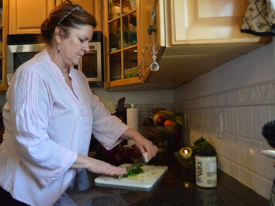 Malia Ricks, owner of Malia's Cafe in Ocean City,  chops fresh cilantro in her home in Berlin.