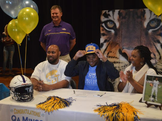 Marksville senior quarterback Qa Mingo (center) dons a Southern cap after signing as a preferred walk-on Thursday.