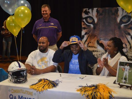 Marksville senior quarterback Qa Mingo (center) dons
