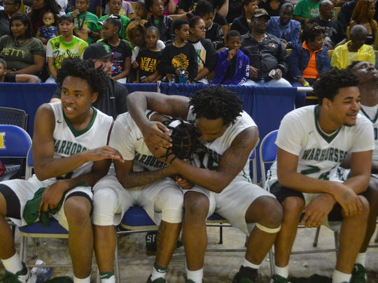 Peabody's Cedric Russell (second left) is consoled by teammates Thomas Miles (left) and Terrell McGee after winning the Class 3A title Saturday.