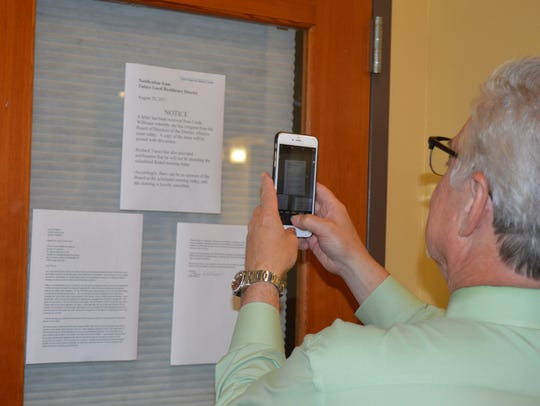 A hospital board meeting attendee takes a picture of