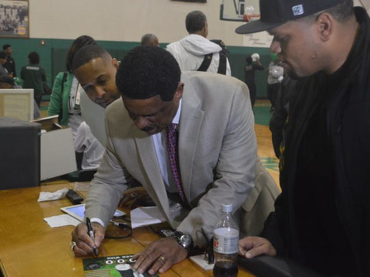 Peabody coach Charles Smith signs autographs Friday.
