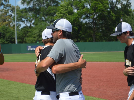Harrisonburg junior Avery Smith (left) hugs his coach Clay McGuffee after the Bulldogs won the Class C title Friday.