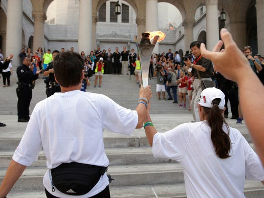 Torchbearers carrying the Flame of Hope walk up the
