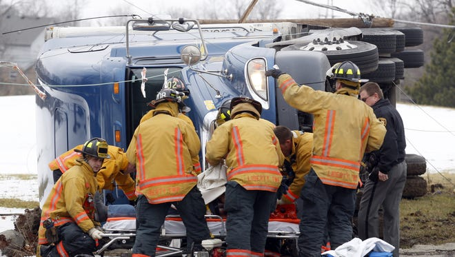 Members of the Liberty Township Fire Department free the driver of a semi truck after crashing into a utility pole on Princeton Road west of Ohio 747 in Liberty Township in 2010.