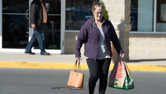 A shopper carries her bags to her car at Tanger Outlets Surfside location in Rehoboth.