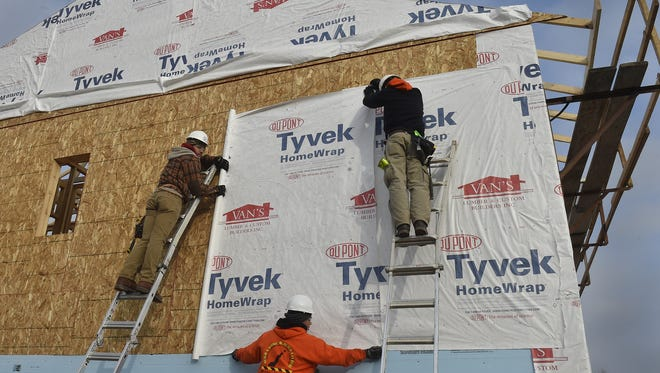 High School students Jaeger Brusky, from left, Erik Escalera and Caleb Diller, all of Sturgeon Bay High School, attach Tyvek HomeWrap to the new single-family home at 344 N. 19th Ave., Sturgeon Bay.