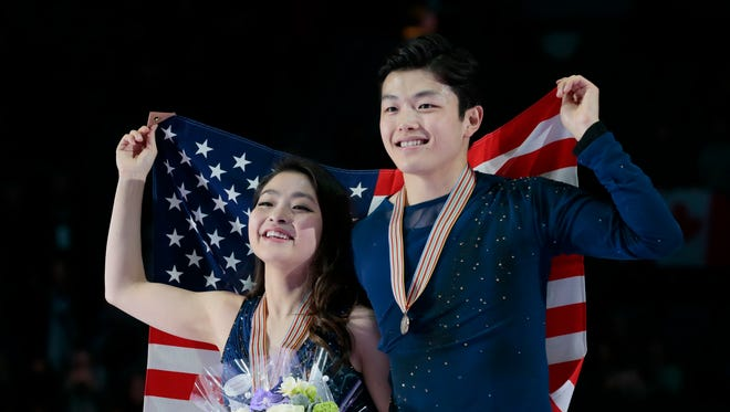 Maia Shibutani and Alex Shibutani, of the United States, pose with their bronze medals and the national flag during victory ceremony at the World figure skating championships in Helsinki, Finland, on Saturday, April 1.