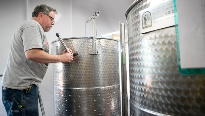 Manager of Sunset Point Winery Gary Johnson prepares to add a yeast nutrient to a sauvignon blanc in the production room at Sunset Point winery in Stevens Point, Wednesday, May 20, 2015.
