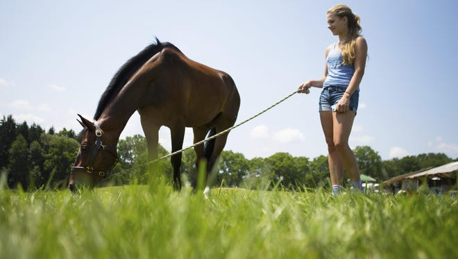 Katie Cantine of Lebanon, New Jersey stands with Loki as he grazes at the Cosequin Stuart Horse Trials on July 11, 2015.