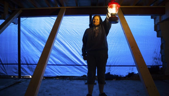 Mary Houck holds a lantern as she stands in the basement of her home in Farmington on July 15, 2015. Houck is living in the home without hot water and electricity is only available for certain appliances in her home.