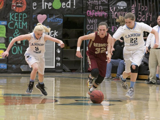 Morgan Myers (middle) chases a loose ball in a basketball