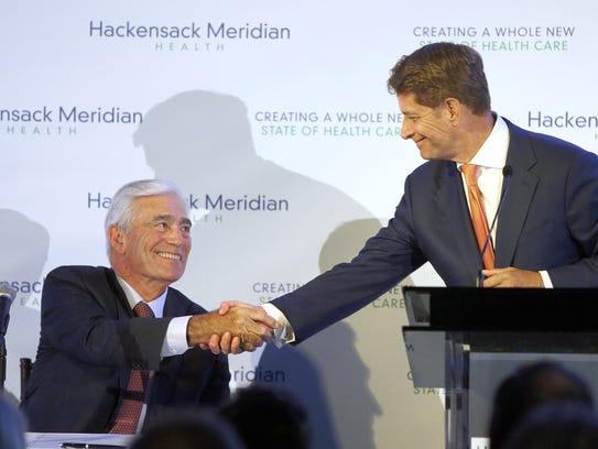 John K. Lloyd (left), Meridian president and CEO, shakes
