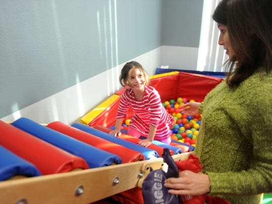 Katherine Rosenthal, of Camarillo, works with Laura Diamond, a speech therapist at the new Easterseals facility in Oxnard. Diamond incorporates the Sensory Gym into Katherine's therapy to make it more fun.