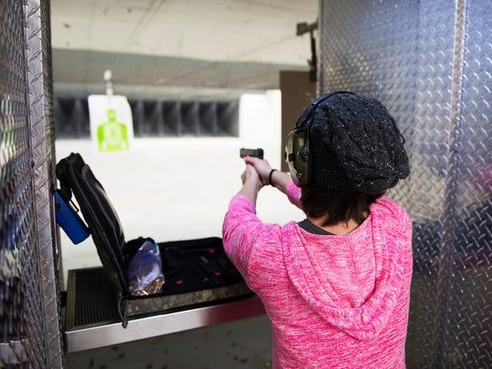 Lydia Vernon fires a handgun at a target at Sharpshooters