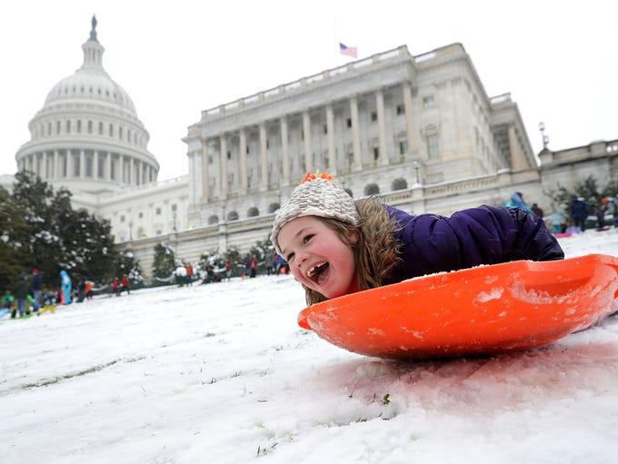 Children sled on the grounds of the U.S. Capitol in
