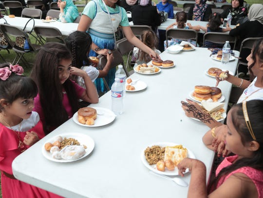 Girls fill their plates with donuts at the Eid al-Fitr