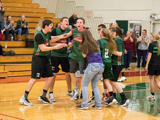 Jonas Hetrick and his Oak Harbor teammates celebrate his buzzer-beating shot to win the 'Can Do! Like You' championship game.
