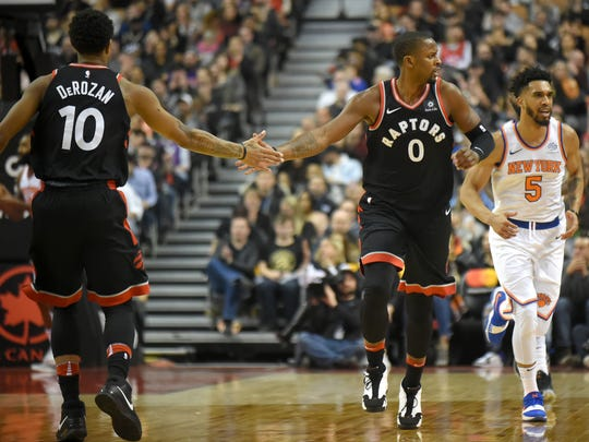 Toronto Raptors guard C.J. Miles (0) slaps hands with guard DeMar DeRozan (10) after making a basket against New York Knicks in the first half at Air Canada Centre at Toronto on Thursday, Feb. 8, 2018.