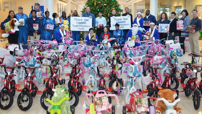 Hyundai Motor Manufacturing Alabama workers and U.S. Marine Corps Reserve representatives, gather for a photo before loading more than 421 bicycles and several boxes of other toys for needy children in the River Region.