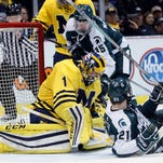 Michigan forward Zach Hyman (11) misplays his shot attempt on Michigan State goalie Jake Hildebrand (30) during the third period of an NCAA college hockey game, Friday, Jan. 30, 2015 in Detroit. Michigan State defeated Michigan, 2-1.