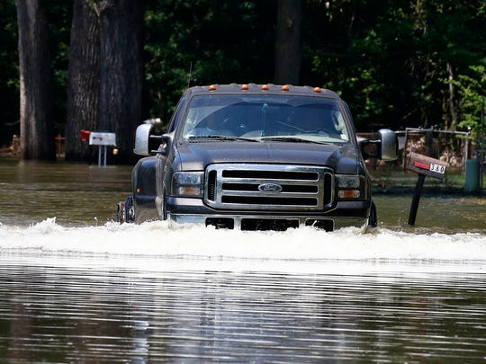 A resident drives his truck from their flooded property along Chickasaw Road in Warren County, near Vicksburg, Miss., Monday, May 15, 2017. MDOT crews will close a section of State Route 465 from U.S. Highway 61 to the backwater levee in Warren County on Tuesday, based on the Mississippi River's forecasted crest of 48 feet on May 19, at Vicksburg. (AP Photo/Rogelio V. Solis)