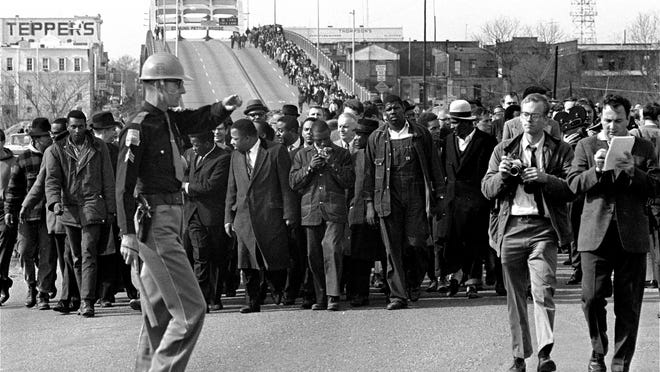 FILE: Demonstrators, including Dr. Martin Luther King, Jr., stream over an Alabama River bridge at the city limits of Selma, Ala., in this March 10, 1965 file photo, during a voter rights march. (AP Photo, File)