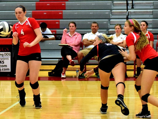 Kylee Howard (2) of Oak Hills keeps service alive as she is held up by teammate Abby Hulsman (right),  September 8.