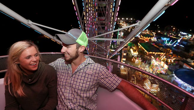 Amber Dozier and her boyfriend Dane Elwood ride the giant ferris wheel overlooking the lights of the North Florida Fair during opening day on Thursday, Nov. 2, 2017.