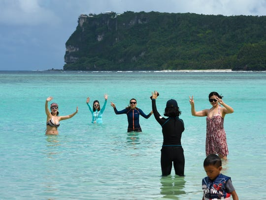 Two Lovers' Point serves as a background for tourists posing for a photo in the water off Matapang Beach on Friday, Oct. 28, 2016.