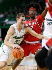 Marshall's Jon Elmore (33) attempts to cut to the basket while defended by Western Kentucky's Taveion Hollingsworth (13) during a game  Jan. 6.
