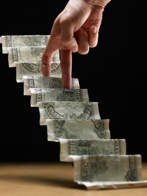 hand climbing up stairs made of dollar bills