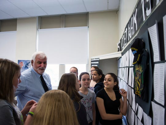 History teacher Joe Knazek speaks with students next to the replica Vietnam War memorial they helped to create last month.