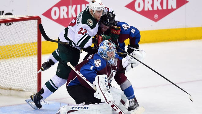 Minnesota Wild right wing Nino Niederreiter (22) commits a penalty on Colorado Avalanche defenseman Tyson Barrie (4) as goalie Semyon Varlamov (1) defends his net in the second period.