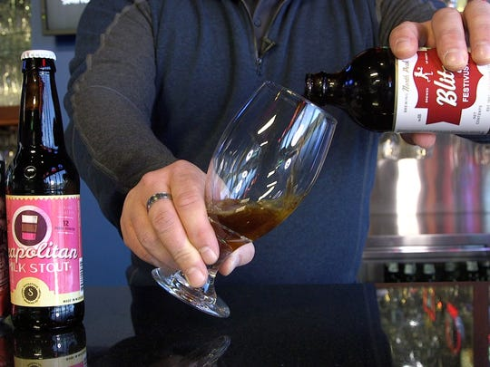 Bobby Vedder, a certified cicerone from Powers Distributing in Orion Township, pours a Blitzen Festivus Ale from North Peak Brewing Company in Traverse City.