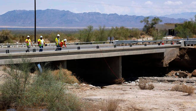 Inspectors for the California Department of Transportation inspect a west-bound bridge for damage next to the bridge that was washed out along Interstate 10 in Southern California, Monday, July 20, 2015.