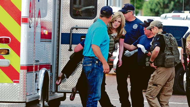An injured woman is carried to an ambulance in Clovis, N.M., Monday, Aug. 28, 2017, as authorities respond to reports of a shooting inside a public library. A city official says police have taken a person into custody who they believe is responsible for a shooting at the library. (Tony Bullocks/The Eastern New Mexico News via AP) ORG XMIT: NMCLO101